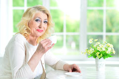 Senior woman with cup of tea. Senior woman sitting at table with cup of tea Stock Image