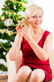 Senior woman is curious about Christmas gift Royalty Free Stock Photos