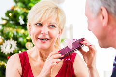 Senior woman is curious about Christmas gift. Senior women is happy and curious about Christmas gift Royalty Free Stock Photos