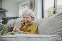 Enjoying a Phonecall And A Cup Of Tea. Senior woman is curled up on the sofa in her home with a cup of tea while she enjoys a phonecall on a smartphone Royalty Free Stock Images