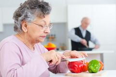 Senior woman cutting capsicums while husaband cooks in background Royalty Free Stock Images