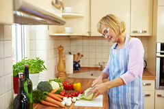 Senior Woman Cutting Kohlrabi Stock Photo