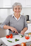 Senior woman cutting vegetables in kitchen Royalty Free Stock Photo
