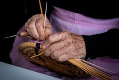 Senior woman knitting a traditional basket with reeds stock photography