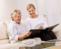 Senior woman and daughter looking at photographs Royalty Free Stock Photography