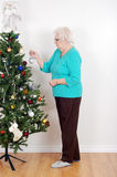 Senior woman decorating her christmas tree Royalty Free Stock Photo