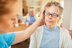 Senior woman with dementia is comforted. Senior women with dementia in the elderly care is comforted by a nursing assistant stock image