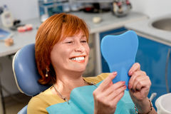 Senior woman in the dental office. Smiling senior woman with new dental implants sitting in the dental office and looking at the mirror royalty free stock photo