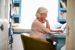 Senior Woman At Desk Working In Home Office With Laptop Stock Images