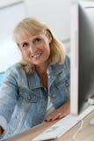 Senior woman on desktop computer Stock Photos