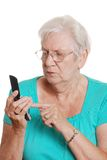 Senior woman dialing a number on cellphone Stock Image