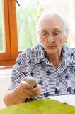Senior Woman Dialling Number On Mobile Phone Stock Photos