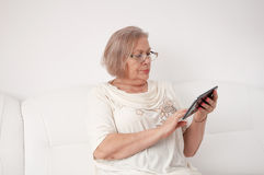 Senior  woman with a digital tablet. Senior  woman use a digital tablet on white couch Royalty Free Stock Image