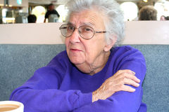 Senior Woman at Diner. Senior citizen woman sitting in a diner booth with a cup of coffee in front of her Stock Images