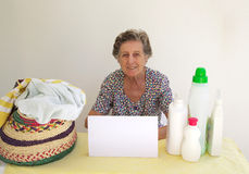 A senior woman, dirty cloths and detergents Royalty Free Stock Images