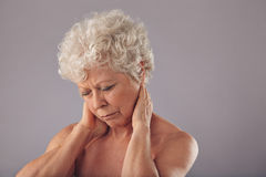 Senior woman in discomfort with sore neck. Portrait of senior woman rubbing her sore neck against grey background. Old woman suffering from neck. Discomfort with stock photos