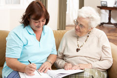 Senior Woman In Discussion With Health Visitor Stock Photo