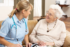 Senior Woman In Discussion With Health Visitor. At Home royalty free stock photography