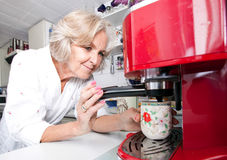 Senior woman dispensing coffee from machine at kitchen counter. Senior women dispensing coffee from machine at kitchen counter Royalty Free Stock Photography