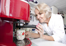 Senior woman dispensing coffee from machine at kitchen counter Stock Photos