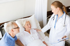 Senior woman and doctor with clipboard at hospital Royalty Free Stock Photos