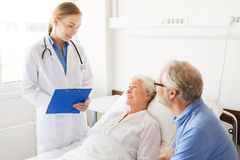 Senior woman and doctor with clipboard at hospital Stock Photos