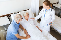 Senior woman and doctor with clipboard at hospital Stock Photo