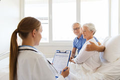 Senior woman and doctor with clipboard at hospital Royalty Free Stock Image