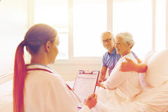 Senior woman and doctor with clipboard at hospital Royalty Free Stock Images