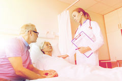 Senior woman and doctor with clipboard at hospital Stock Image