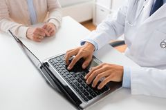 Senior woman and doctor with laptop at hospital. Medicine, healthcare and technology concept - close up of doctor with laptop computer and senior woman at stock photography