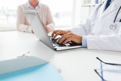 Senior woman and doctor with laptop at hospital. Medicine, healthcare and technology concept - close up of doctor with laptop computer and senior woman at royalty free stock images
