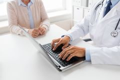 Senior woman and doctor with laptop at hospital. Medicine, healthcare and technology concept - close up of doctor with laptop computer and senior women at stock image