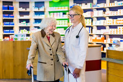 Senior woman and doctor laughing in pharmacy Royalty Free Stock Images