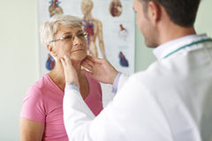 Senior woman at doctor's office. She has problems with sore throat Royalty Free Stock Photo