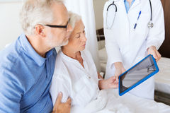 Senior woman and doctor with tablet pc at hospital Stock Images