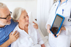 Senior woman and doctor with tablet pc at hospital Stock Photo