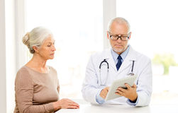 Senior woman and doctor with tablet pc Stock Images