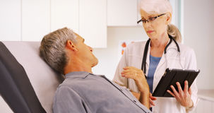 Senior woman doctor talking with elderly man patient in the office royalty free stock photos