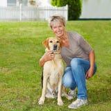 Senior woman with dog in garden Stock Photos