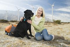 Senior Woman With Dog Near Wind Farm. Portrait of a beautiful senior women sitting with dog near wind farm Stock Image