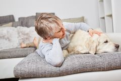Senior woman with dog Retriever. On the couch for relaxation Royalty Free Stock Photo