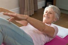 Senior woman doing abs royalty free stock image