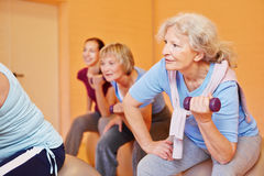 Senior woman doing back exercises. Smiling senior women in a group doing back training exercises with dumbbells Royalty Free Stock Image