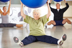 Senior woman doing back traing. Senior women doing back traing with gym ball in a fitness center Royalty Free Stock Photo