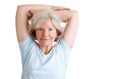 Senior woman doing back training. Happy elderly woman exercising her back with gymnastics Royalty Free Stock Image