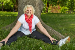 Senior woman doing back training in nature. Happy senior woman doing back training in nature in a park Stock Images