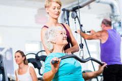 Senior woman doing back training with trainer in gym. Senior women doing back training with trainer in gym at machine Stock Photo