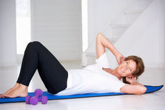 Senior woman doing curl-ups Stock Photos