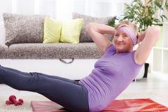 Senior woman doing curl-ups Stock Photos
